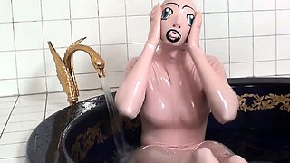 Tanja takes a bath in her latex sex doll costume
