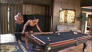 Muscular fellow gives some lessons of pool to ebony chick