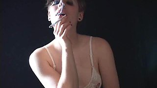 A hot lady playing with her breasts while smoking sexily