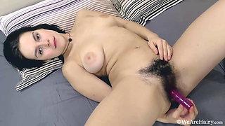 Hairy Ole Nina masturbates in bed with her purple vibrator